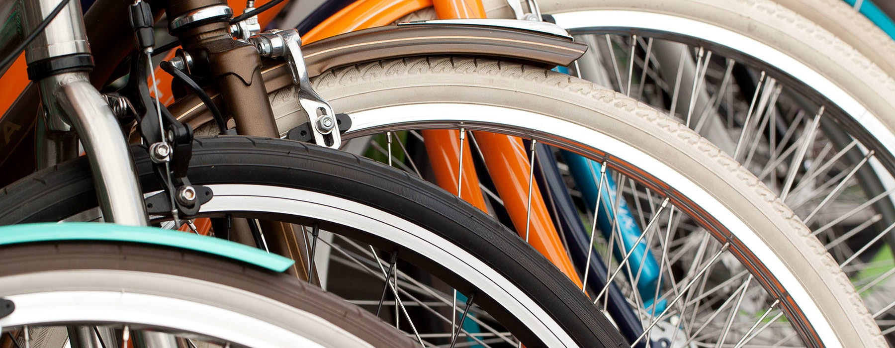 close up of the front tires of bicycles lined up in a row
