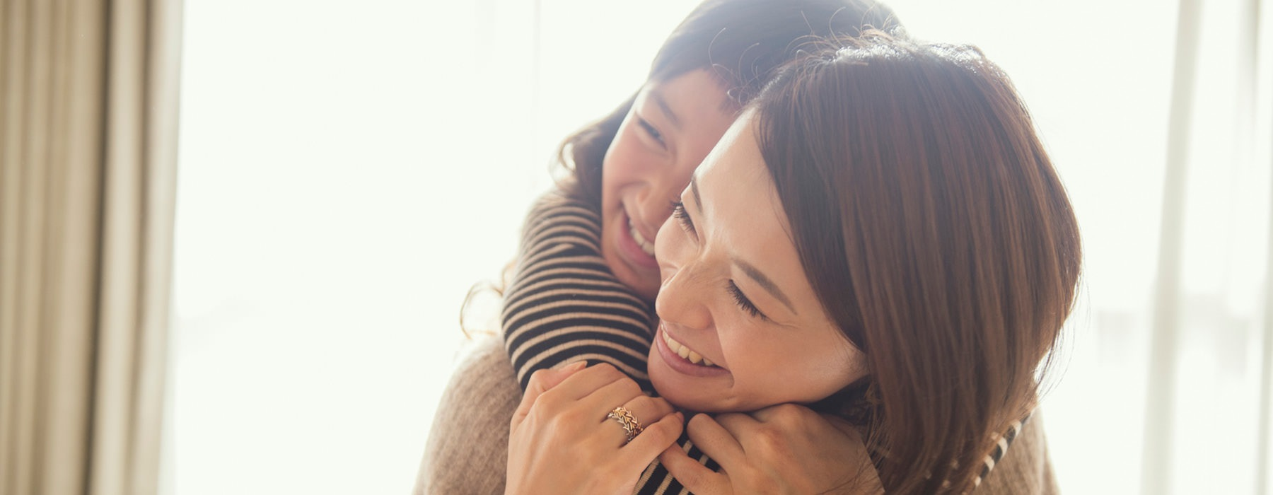 daughter's arms around her mother's neck as both smile in their bright living room