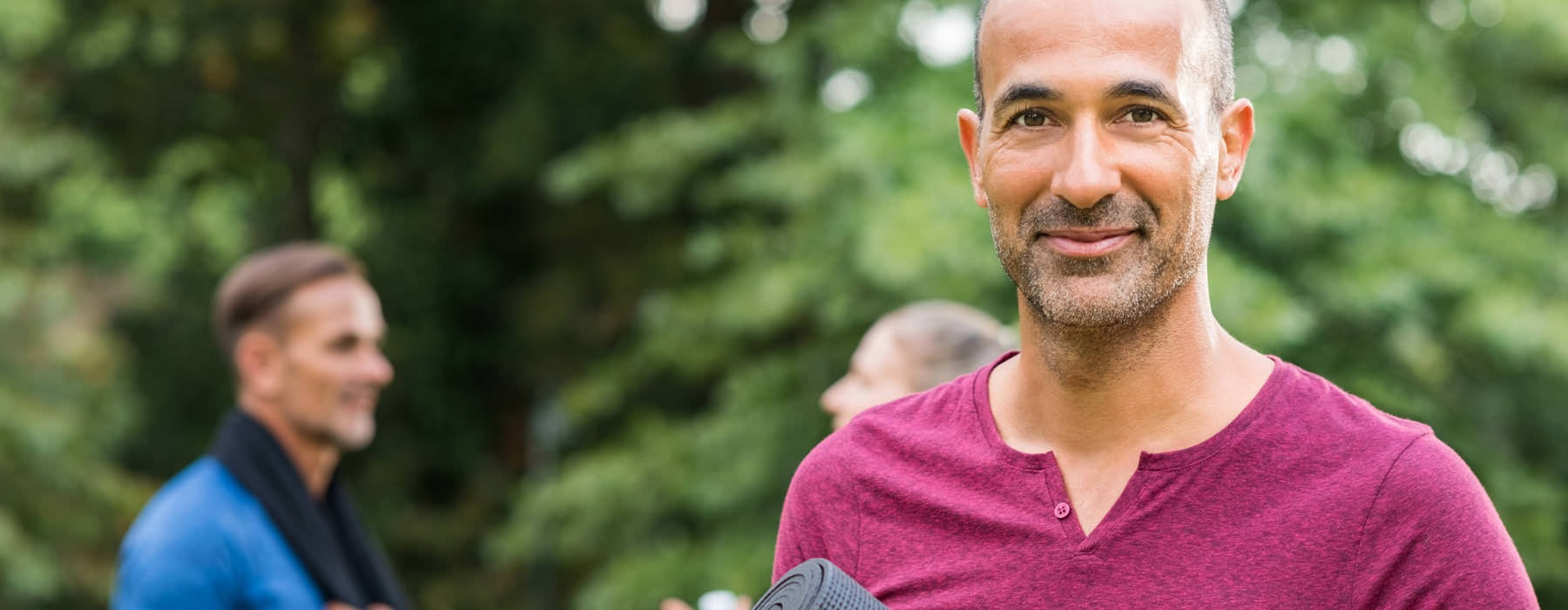 smiling man holds yoga mat in park with friends talking behind him